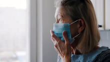 Elderly Lonely Woman Putting On Medical Mask Over Her Face. High Quality Photo