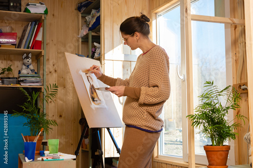 Fotografija Girl artist draws on an easel at home, molubert stands at the window
