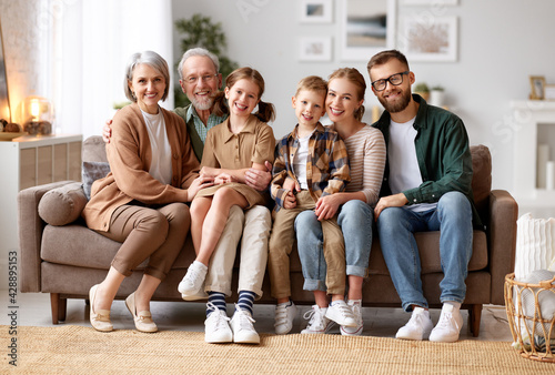 Beautiful multi generational family sitting together on couch at home and smiling at camera