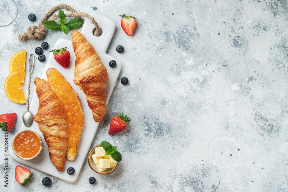 Fotografia Fresh sweet croissants with butter and orange jam for breakfast