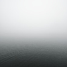 A View Of The Sea. Thick Fog. Symmetry Reflections On The Water. Natural Mirror. Dark Atmospheric Landscape. Abstract Art, Texture, Background, Wallpaper, Grey Color, Monochrome, Black And White