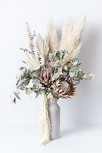 Beautiful Dried Flower Arrangement In A Stylish Pink Vase. In The Flower Bunch Is Pink King Proteas, Palm Frond, Eucalyptus Leaves, Amaranthus And Pampas Grass, Photographed On A White Background.