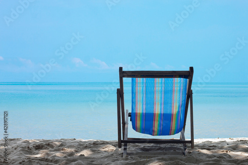 Fotografering A deck chair on the tropical sand  beach and bright sky over calm sea give you a feeling of relaxation during the holidays