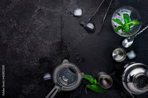 Steel bar tools and accessories for making cocktail. Shaker, jigger, strainer, spoon, tongs, muddler. Alcohol drink and beverages preparation concept. Black background, top view, copy space