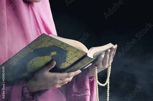 Muslim woman in a veil holding prayer beads and the Quran