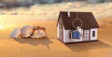 Model Of House And Key With Sea Shells On Sandy Beach
