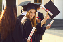 Successful Graduation From University. Smiling Beautiful Girl University Or College Graduate Standing With Diploma And Looking At Camera Over Mates Around And University At Background