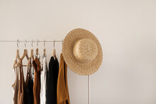 Women's Fashion Bright Pastel Clothes On Clothing Rack On White Background. Minimalist Fashion Blog Concept.
