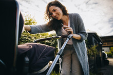 Happy Mother With Stroller Outdoors