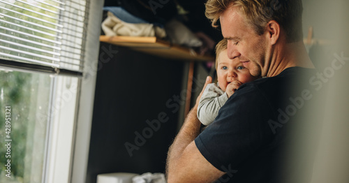 Father consoling his baby at home - fototapety na wymiar