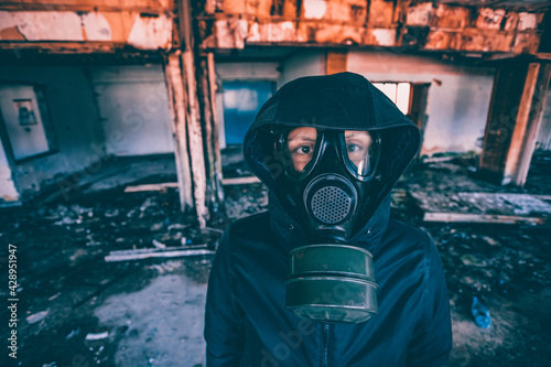 Fotografie, Obraz Dramatic portrait of a woman wearing a gas mask in a ruined building