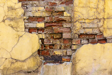 Old Vintage Brick Wall With Crumbling Cracked Yellow Concrete Plaster. Abandoned Building Industrial Background