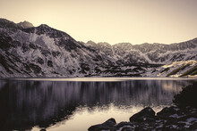 Sepia View Of A Big Mountain Lake In High Tatra Mountains, Poland. The Sun Is Setting Behind A Rocky Ridge. Selective Focus On Water, Blurred Background.