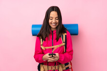 Young Mountaineer Girl With A Big Backpack Over Isolated Pink Background Sending A Message With The Mobile
