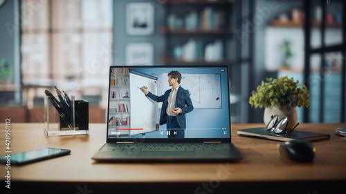 Obraz na plátně Shot of a Laptop Computer Showing Online Lecture with Portrait of a Cute Male Teacher Explaining Math Formulas