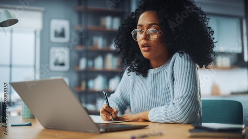 Beautiful Authentic Latina Female Sitting at a Desk in a Cozy Living Room and Following a Video School Lesson on Laptop Computer. Student Studying Remotely. Chat with Friends on Social Network. - fototapety na wymiar