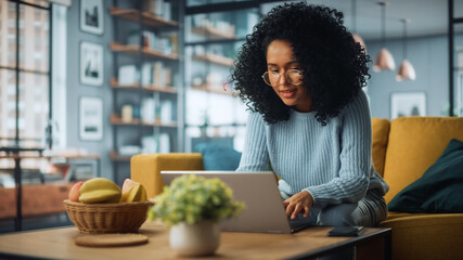 Beautiful Authentic Latina Female Sitting on a Sofa in a Cozy Living Room and Using Laptop Computer at Home. Happy Freelancer Female Browsing Internet and Social Networks.