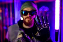 Young Man In Glasses Metallic Robot Hand Showing Gesture Hi In Neon Lights