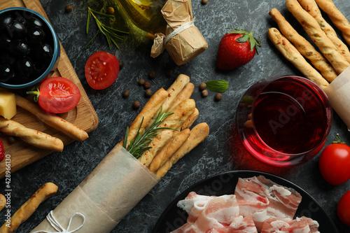 Fototapeta Grissini sticks, snacks and wine on black smokey background obraz