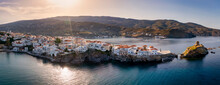 Panoramic View To The Town Of The Greek Island Andros, Aegean Sea, Situated On A Long Stretch Into The Sea During Sunset Time