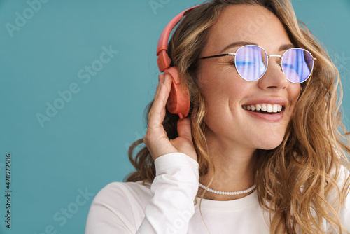 Fotografia Smiling young blonde woman in glasses listening to music