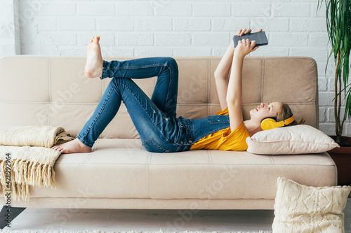 Fotografia, Obraz Teenage girl in denim overalls relaxes in pleasure on the couch with an electronic tablet