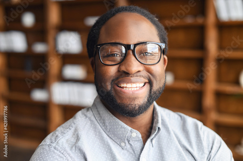Obraz Close-up portrait of a happy African-American young man with friendly wide toothy smile, a mixed-race bearded guy wearing stylish eyeglasse and shirt looks into camera, employee profile photo - fototapety do salonu