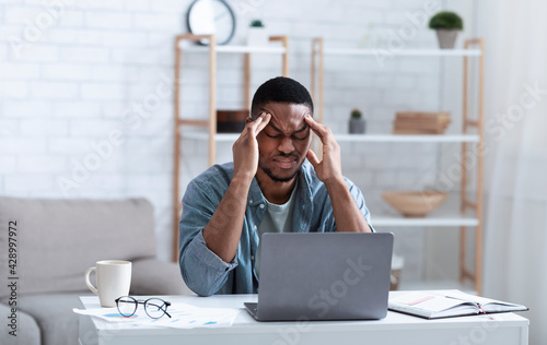 Canvas Print African American Businessman Having Headache Sitting At Laptop Indoor