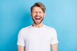 Leinwandbild Motiv Photo portrait of young man in casual t-shirt laughing with opened mouth isolated bright blue color background
