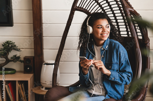 Fotomural Young beautiful african-american woman listening to the music in the rocking chair in cosy flat