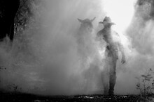 A Black And White Photo Of A Cowboy Walking With A Trusty Horse.