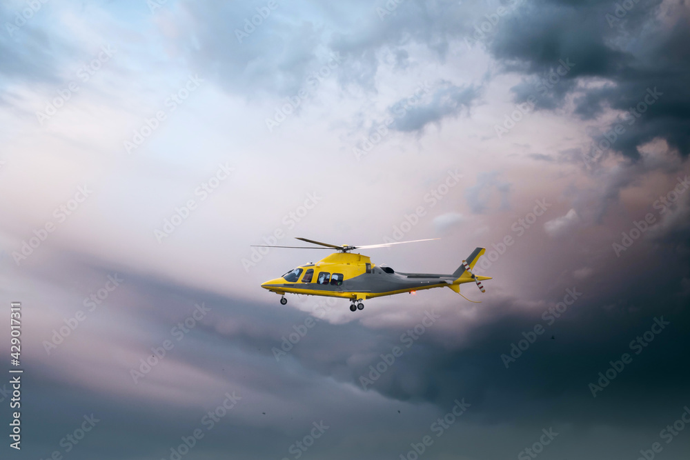 Fototapeta Air Ambulance helicopter yellow medical emergency chopper taking off at dusk amazing dramatic storm sky as respond to 999 incident medic team