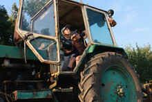 The Boys Are Playing And Looking At A Large Farm Tractor.