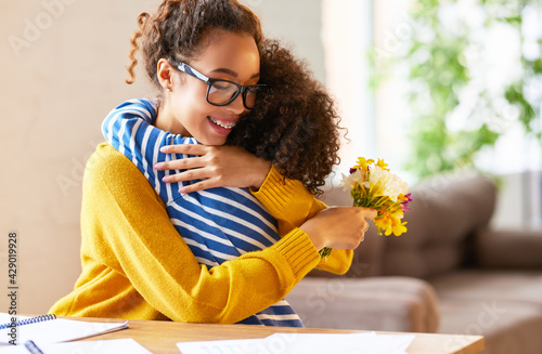 Obraz Happy mixed race woman mother with flower bouquet embracing with child while getting congratulations on Mothers day - fototapety do salonu