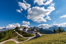 Lussari Village Or Monte Santo Di Lussari (1790 M) With The Mountain Range Of Mangart, Jof Di Montasio, Jof Fuart And The Cima Del Cacciatore (Peak Of The Hunter). Friuli Venezia Giulia, Italy.