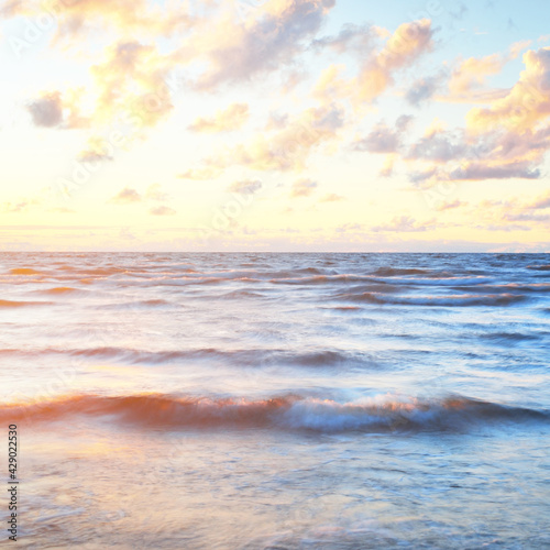 Epic colorful glowing pink sunset clouds above the sea after a thunderstorm. Dramatic sky. Waves and water splashes texture. Idyllic seascape. Concept image, long exposure. Picturesque scenery