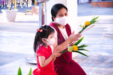 Family Wearing Mask Is Going To Pay Homage To Monks At Temple. Mother And Daughter Hands Holding Flowers. Prevent Spread Of Virus And Air Pollution. Make Merit During The Chinese New Year.
