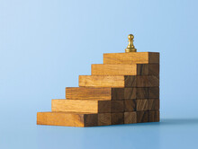 Business Growth, Business Success Or Career Path Success Concept. A Pawn Chess Is On The Top Of Wooden Stacked Staircase In Blue Scene Background.