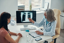 Mature Female Doctor In White Lab Coat Showing To Young Woman Her Lungs Scan While Sitting In Her Office