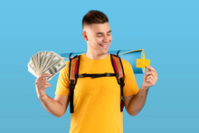 Travel Budget. Portrait Of Cool Young Guy With Rucksack, Credit Card And American Money Over Blue Studio Background