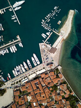 Aerial View Of Old Town, Boats Moored In Dock, Yacht Port In Budva, Montenegro. Ancient Architecture With Orange Roofs, Quay Seafront With Parked Cars, Boats Parking. Sunny Summer. Travel Destination