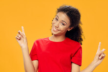 Curly-haired Woman In A Red T-shirt Gesturing With Her Hands On A Yellow Background Copy Space
