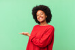 afro black woman smiling cheerfully, feeling happy and showing a concept in copy space with palm of hand
