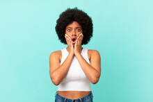 Afro Black Woman Feeling Shocked And Scared, Looking Terrified With Open Mouth And Hands On Cheeks
