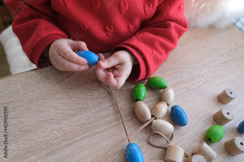 Obraz na plátně small child, toddler stringing colored wooden beads on a string, children's fing