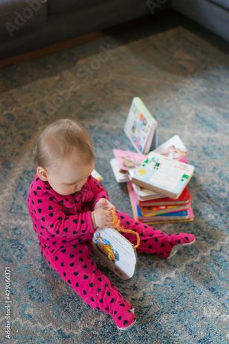 Valokuvatapetti Young baby going through a pile of board books; toddler wearing pink footie paja