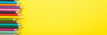 Many New Colorful Pencils On Bright Yellow Table Background. Wide Banner. Closeup. Empty Place For Text. Top Down View.