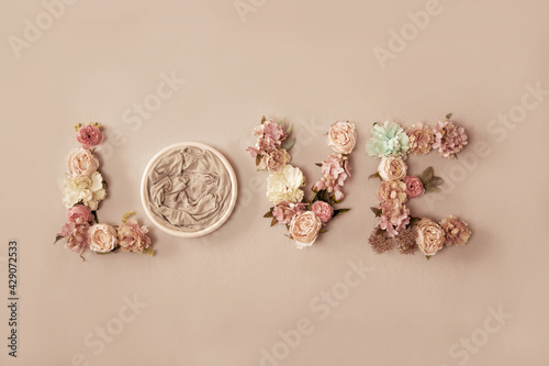 Canvas Print Newborn love background - word Love spelled with flowers and round bowl on light