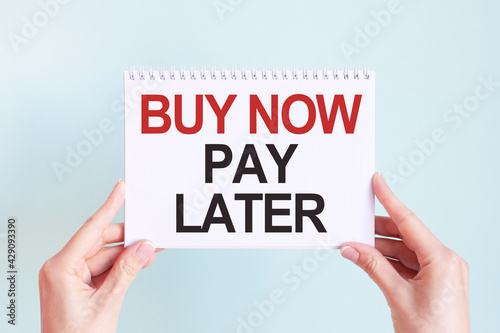 buy now pay later word inscription on white card paper sheet in hands of a woman. Business concept