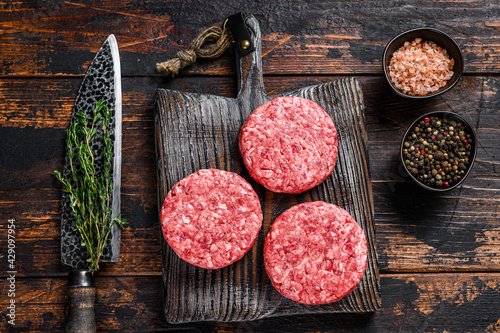 Fotografiet Raw steak burgers patties with ground beef and thyme on a wooden cutting board